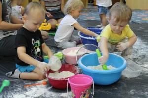 Dzieci wkładające ręce do misek z mąką i wodą