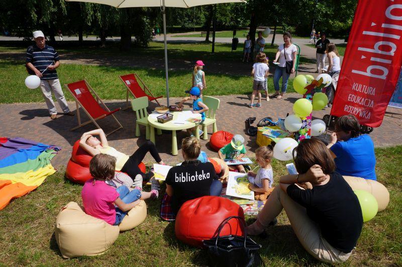 Czytelnicy siedzący na pufach na podwórku