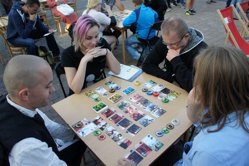 Ludzie przy stole grający w grę karcianą